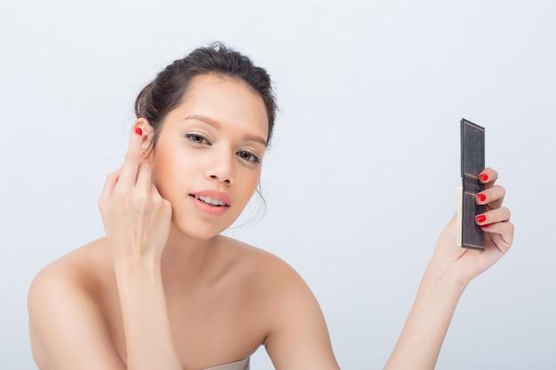 Schöne asiatische frau, die lidschatten-palette mit schönheitsnatur-make-up-frischer weicher haut anwendet