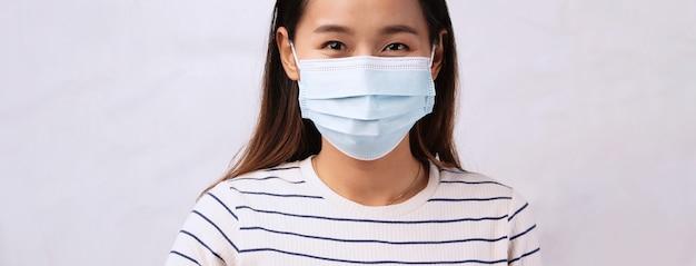 Schöne asiatische frau, die maskenschutzviruskorona oder covid19 trägt. gesundes pflegekonzept