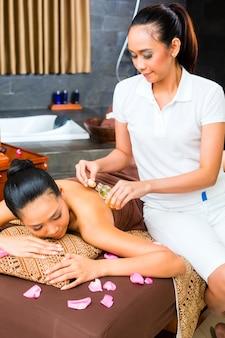 Schöne asiatische frau, die massage empfängt