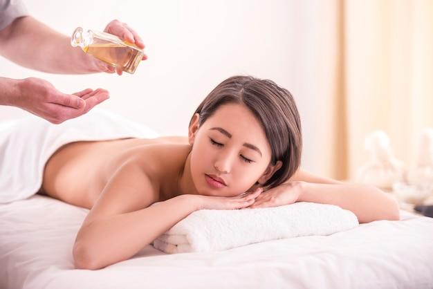 Schöne asiatische frau, die massage mit badekurortöl hat.