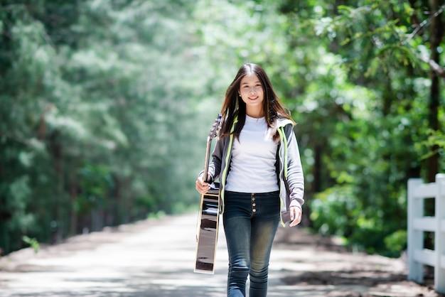 Schöne asiatische frau, die mit akustikgitarre lächelt