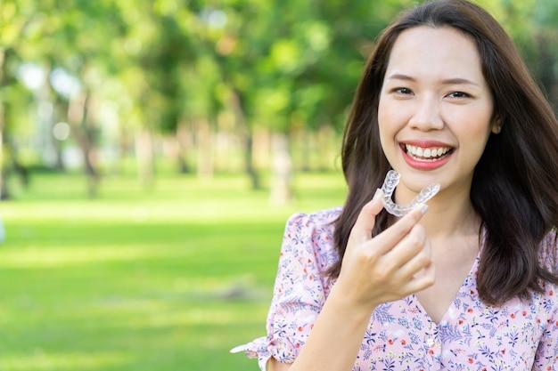 Schöne asiatische frau, die mit der hand hält zahnmedizinischen ausrichtungshalter naturpark am im freien lächelt