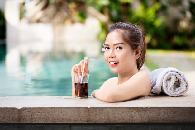 Schöne asiatische frau, die mit getränk sich entspannt