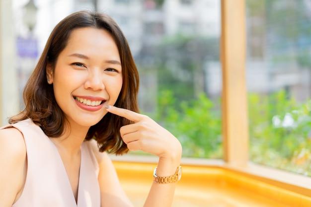 Schöne asiatische frau, die mit glück lächelt und hand verwendet, um auf zähne an der zahnklinik zu zeigen