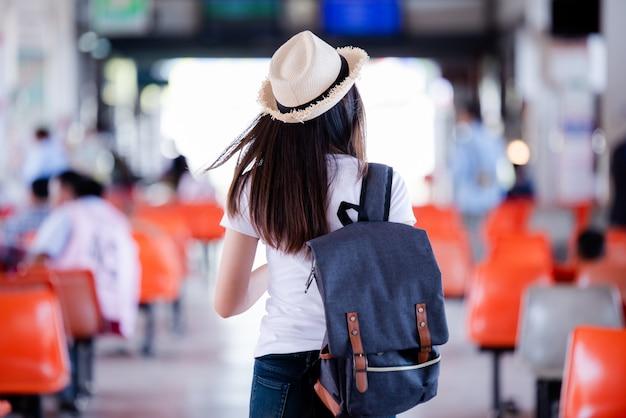 Schöne asiatische frau, die mit karte und tasche am busbahnhof lächelt