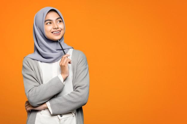 Schöne asiatische frau, die mit lächelndem gesicht denkt und nach oben schaut