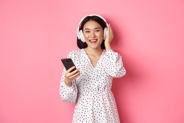 Schöne asiatische frau, die musik in kopfhörern hört, handy benutzt, glücklich in die kamera lächelt und über rosafarbenem hintergrund steht