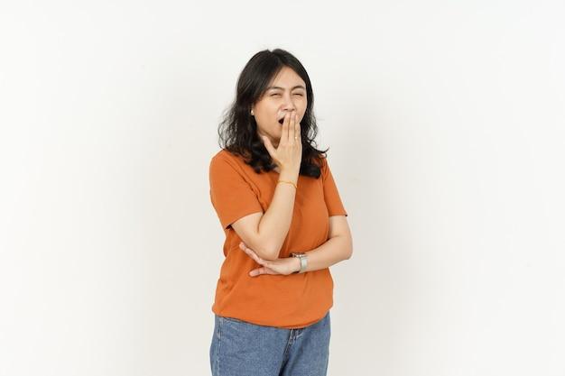 Schöne asiatische frau, die orangefarbenes t-shirt trägt gähnen-gestenausdruck