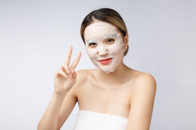 Schöne asiatische frau, die papierblattmaske auf ihrem gesichtsweißhintergrund anwendet