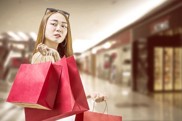 Schöne asiatische frau, die rote papiertüten hält