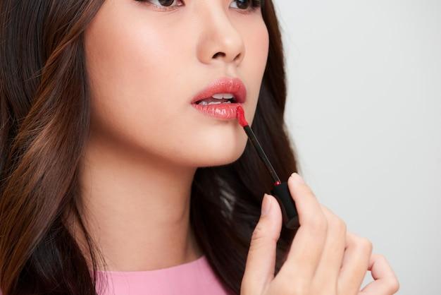 Schöne asiatische frau, die roten lipgloss hält und ihn anwendet