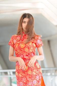 Schöne asiatische frau, die rotes kleid im chinesischen neujahr trägt