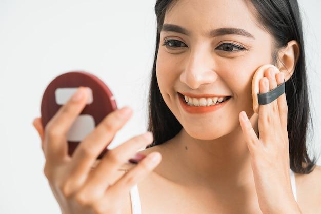 Schöne asiatische frau, die rouge auf ihrem gesicht mit puderquaste und spiegel, hautpflegekonzept auf rosa wand anwendet.