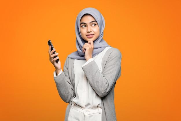 Schöne asiatische frau, die smartphone denkt und hält