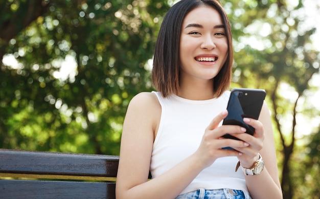 Schöne asiatische frau, die smartphone im park verwendet