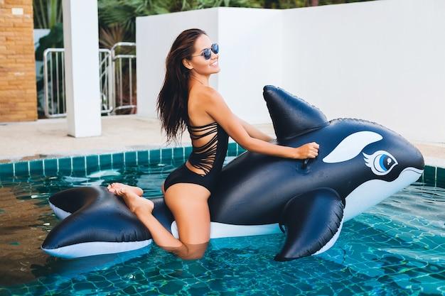 Schöne asiatische frau, die spaß im pool auf tropischer villa in den sommerferien in thailand spielt mit dem großen orca trägt schwarzen badeanzug und sonnenbrille, sexy körper, modeaccessoires