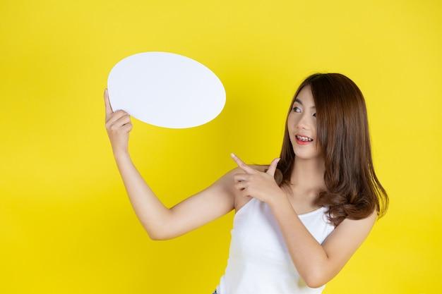 Schöne asiatische frau, die sprachblase mit leerem raum für text auf gelber wand hält und aufblickt