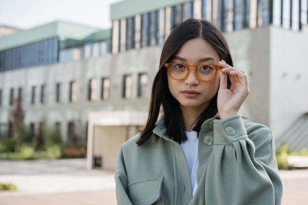 Schöne asiatische frau, die stilvolle brillen trägt, die kamera betrachten