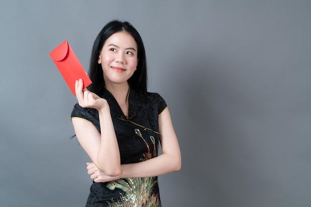 Schöne asiatische frau, die traditionelle chinesische kleidung mit rotem umschlag oder rotem paket auf grau trägt