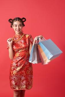 Schöne asiatische frau, die traditionelles cheongsam qipao kleid trägt, das einkaufstaschen und goldhalskette auf roter wand für chinesische neujahrseinkaufskonzepte zeigt.