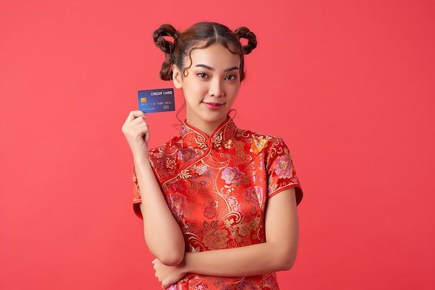 Schöne asiatische frau, die traditionelles cheongsam qipao kleid trägt, das kreditkarte auf roter wand für chinesische neujahrseinkaufskonzepte zeigt,