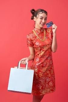 Schöne asiatische frau, die traditionelles cheongsam qipao-kleid trägt, das kreditkarte, einkaufstaschen und goldhalskette auf roter wand für chinesische neujahrseinkaufskonzepte zeigt.