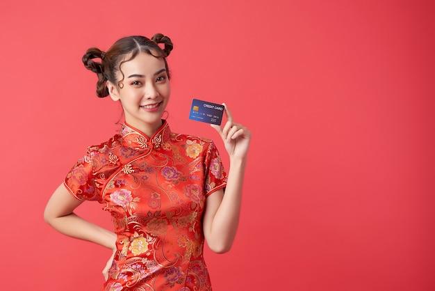 Schöne asiatische frau, die traditionelles cheongsam qipao kleid trägt, das kreditkarte für chinesische neujahrseinkaufskonzepte zeigt,
