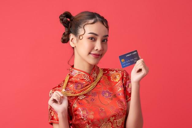 Schöne asiatische frau, die traditionelles cheongsam qipao kleid trägt, das kreditkarte und goldhalskette auf roter wand für chinesische neujahrseinkaufskonzepte zeigt
