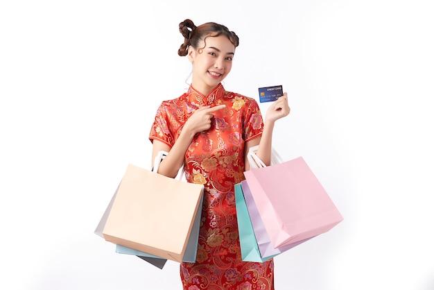 Schöne asiatische frau, die traditionelles cheongsam qipao kleid trägt, das kreditkarte und mit einkaufstasche in der hand für chinesische neujahrseinkaufskonzepte zeigt.