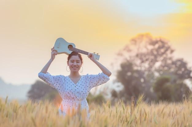 Schöne asiatische frau, die ukulele hält und am gerstenfeld im sommer auf sonnenuntergangzeit sich entspannt