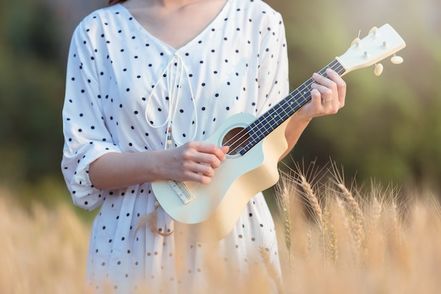 Schöne asiatische frau, die ukulele spielt und am gerstenfeld im sommer auf sonnenuntergangzeit sich entspannt