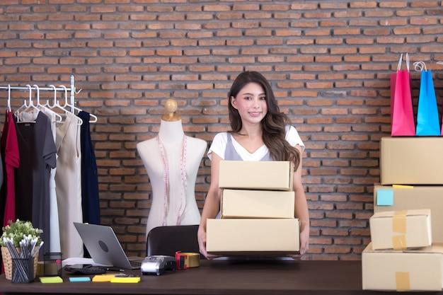 Schöne asiatische frau, die unter mehreren kisten steht und pakete prüft, im hausbüro arbeitend.