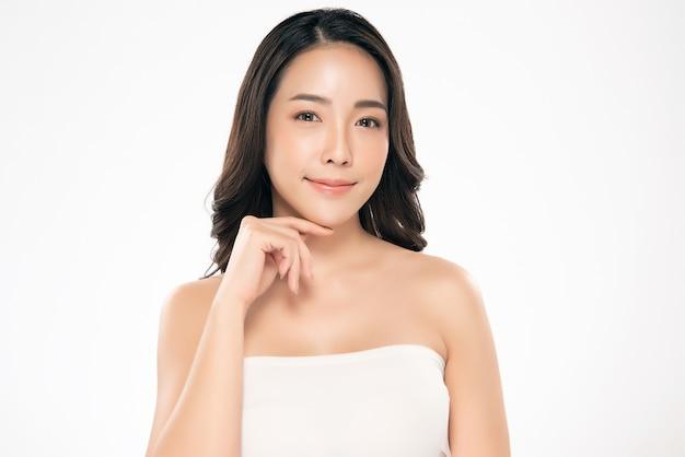 Schöne asiatische frau, die weiches backenlächeln mit sauberem und neuem haut glück berührt
