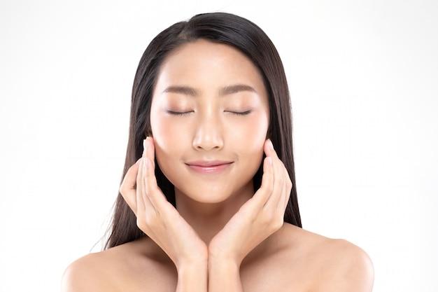 Schöne asiatische frau, die weiches wangenlächeln mit sauberer und frischer haut berührt