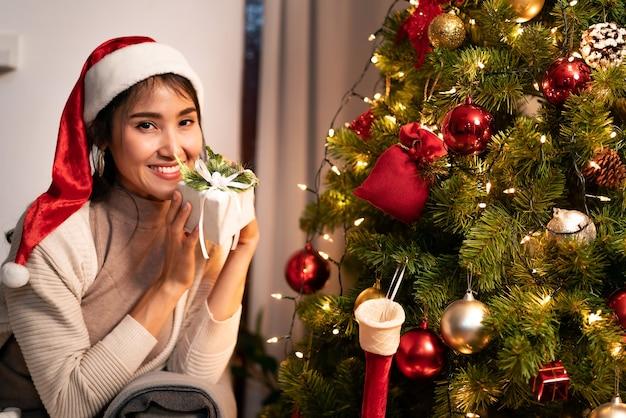 Schöne asiatische frau, die weihnachtsverzierung für verzieren auf weihnachtsbaum hält