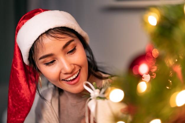 Schöne asiatische frau, die weihnachtsverzierung für verzieren auf weihnachtsbaum hält.