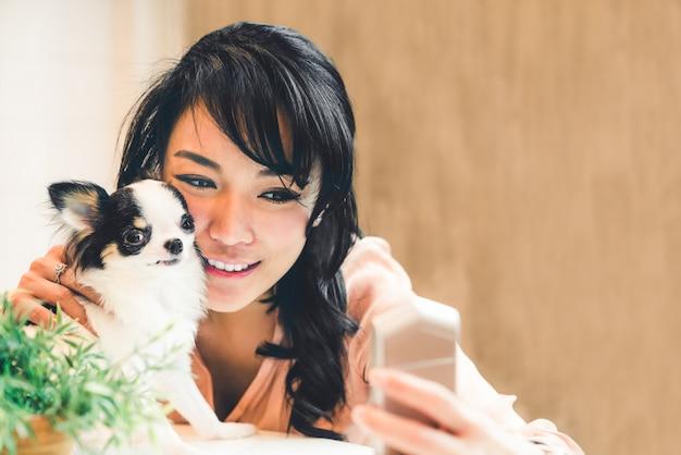 Schöne asiatische frau, die zu hause selfie mit nettem chihuahuahund nimmt