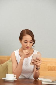 Schöne asiatische frau, die zu hause smartphone verwendet