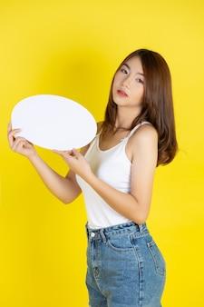 Schöne asiatische frau, die zur sprechblase mit leerem raum hält und schaut