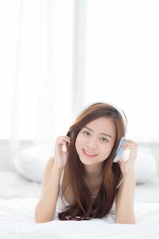 Schöne asiatische frau genießen hören musik mit kopfhörer beim lügen im schlafzimmer