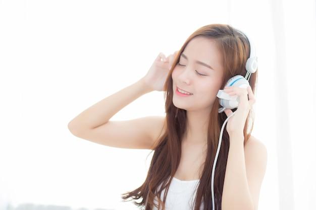 Schöne asiatische frau genießen hören musik mit kopfhörer beim sitzen im schlafzimmer.