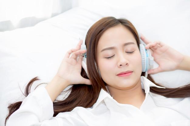 Schöne asiatische frau genießen sie musik mit kopfhörer.