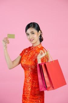 Schöne asiatische frau glückliches lächeln und einkaufen im chinesischen neujahr auf rosa hintergrund.