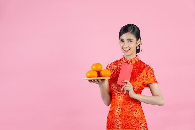 Schöne asiatische frau glückliches lächeln und hält frische orangen im chinesischen neujahr auf rosa hintergrund.