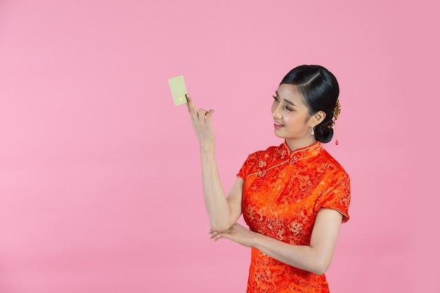 Schöne asiatische frau glückliches lächeln und kreditkarte im chinesischen neujahr auf rosa hintergrund zeigen.