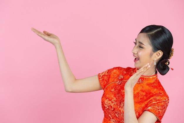 Schöne asiatische frau glückliches lächeln und zeigt ihnen etwas im chinesischen neujahr auf rosa hintergrund
