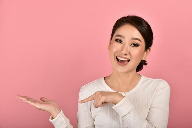 Schöne asiatische frau hand offen und finger zeigen produkt