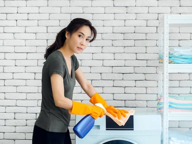 Schöne asiatische frau, hausfrau, die orange schutzgummihandschuhe unter verwendung des saubereren sprays und des sauberen tuches zur reinigung der waschmaschine auf weißer backsteinmauer trägt