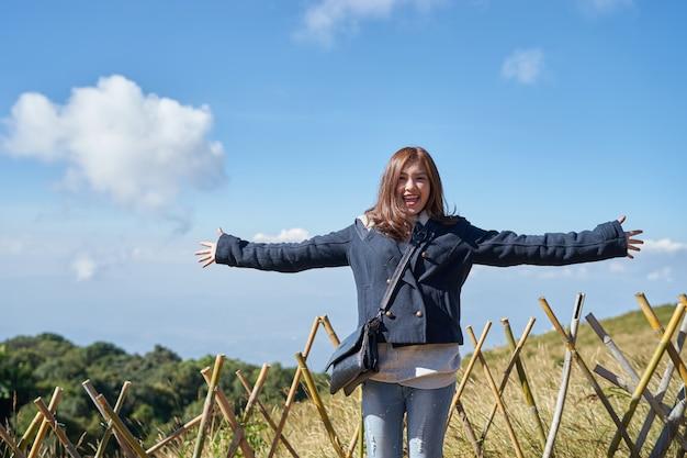 Schöne asiatische frau heben hand an und genießen sie ansicht auf berg und blauen himmel