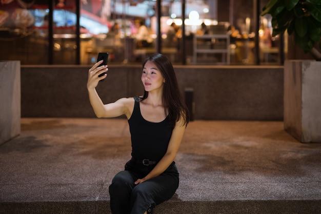 Schöne asiatische frau im freien bei nacht, die selfie mit handy nimmt